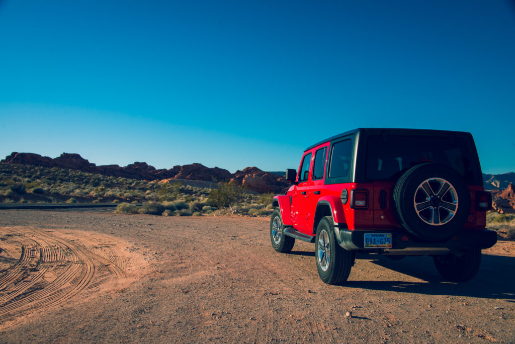 a red 2019 jeep wrangler sits on a dirt road at valley of fire state park in nevada, photographed by jamie bannon photography.