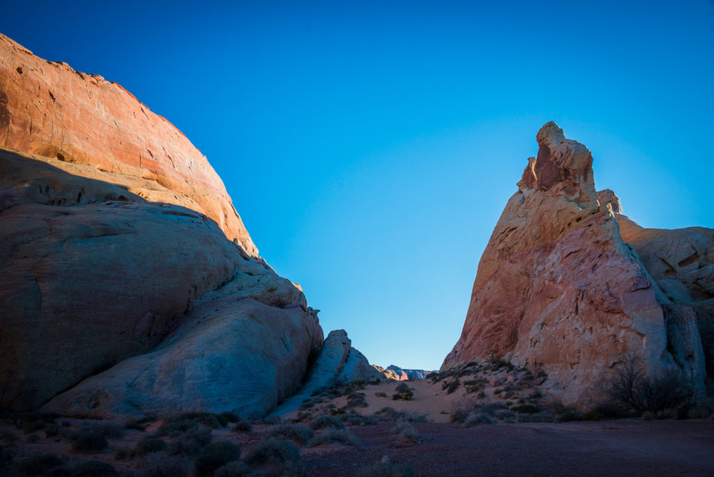 sunlight casts dramatic blue shadows on the red rocks of valley of fire state park in nevada at sunset, photographed by jamie bannon photography.