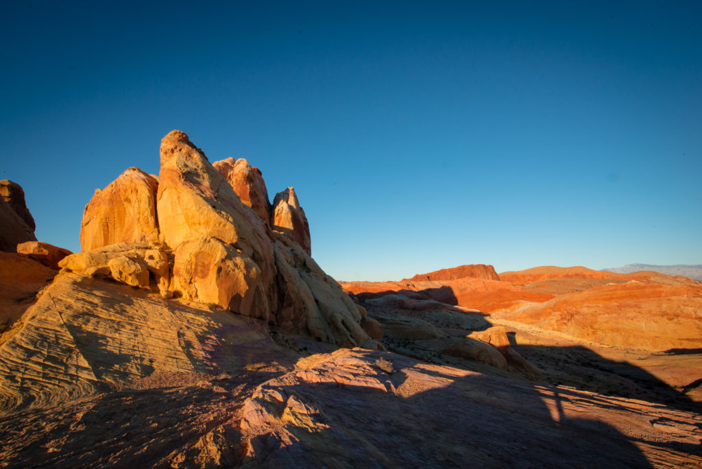sunlight casts dramatic shadows on the textured red rocks of valley of fire state park in nevada at sunset, photographed by jamie bannon photography.