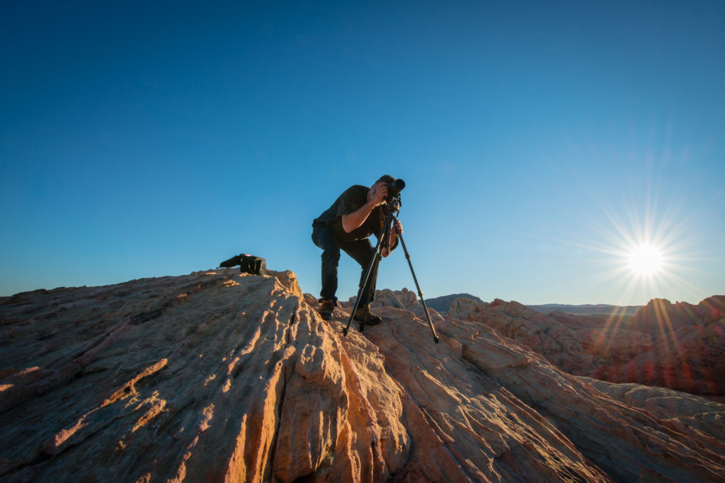 a photographer takes a picture as the sun sets over the red rocks at valley of fire state park in nevada , photographed by jamie bannon photography.