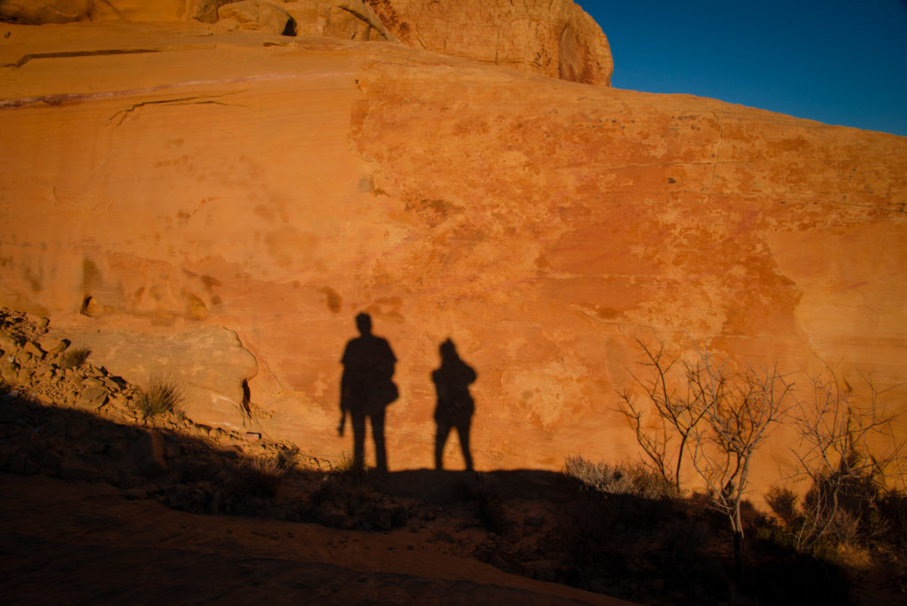 sunlight casts a shadow of two photographers on a large red rock at valley of fire state park in nevada at sunset, photographed by jamie bannon photography.