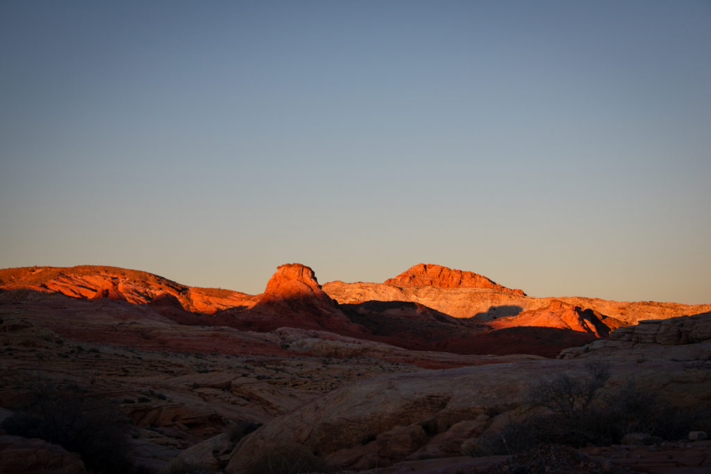 sunlight casts dramatic shadows on the red rocks of valley of fire state park in nevada at sunset, photographed by jamie bannon photography.