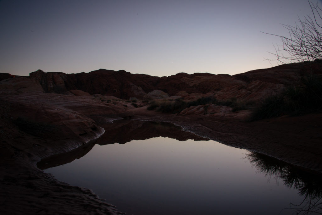 a small pond reflects the sky and mountain landscape at valley of fire state park in nevada at dusk, photographed by jamie bannon photography.