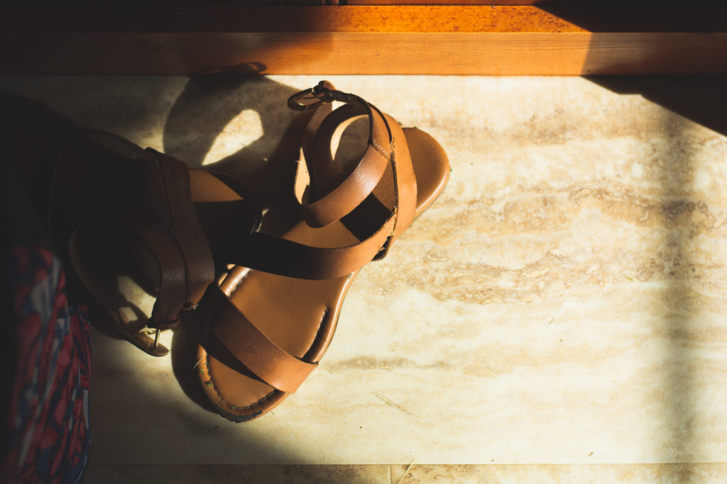the sun lights a sandal on the floor of a beach house in niantic, connecticut, photographed by jamie bannon photography.