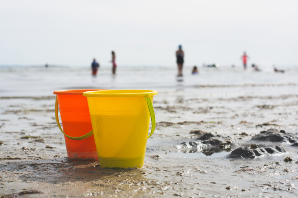 a yellow and orange pail sit on the sand at rocky neck beach in niantic, connecticut, photographed by jamie bannon photography.