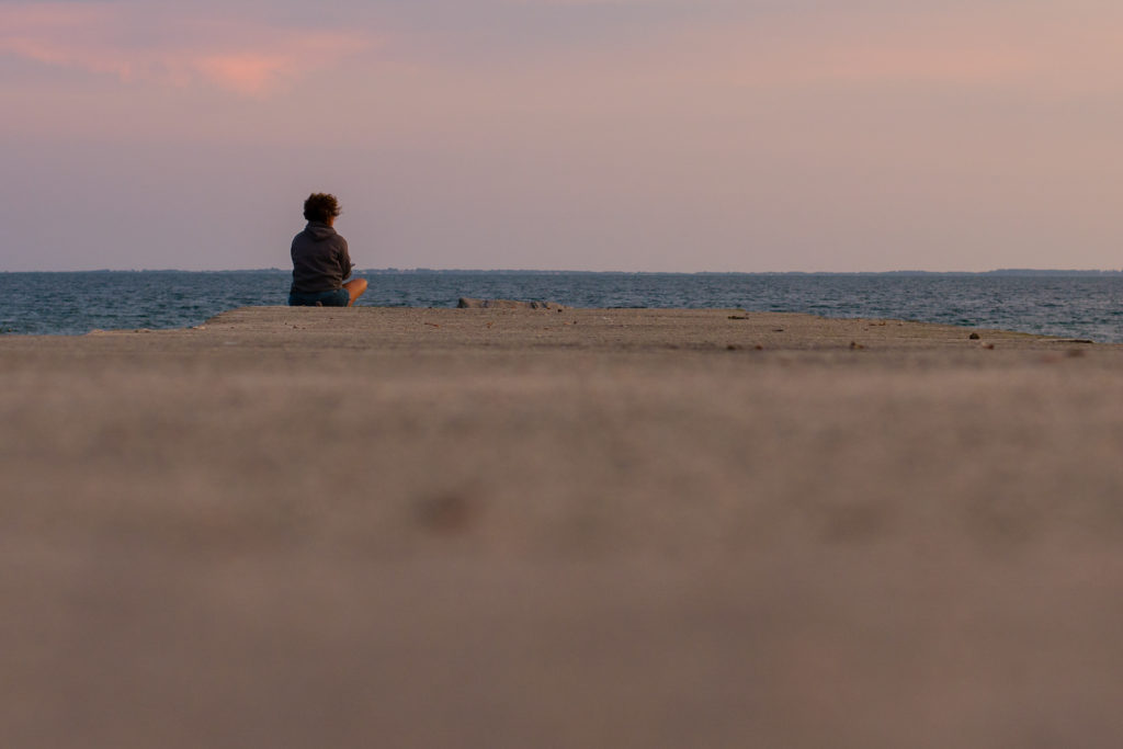 a woman sits alone on the jetty at sunset in niantic, connecticut, photographed by jamie bannon photography.