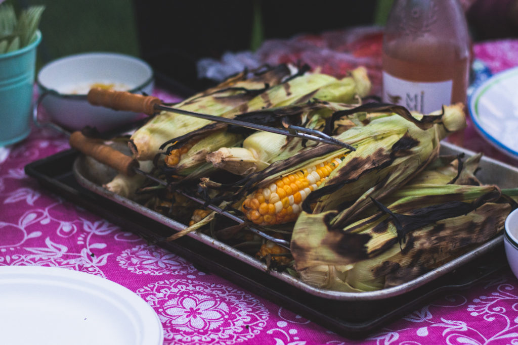 grilled corn sits on the dinner table outside, photographed by jamie bannon photography.