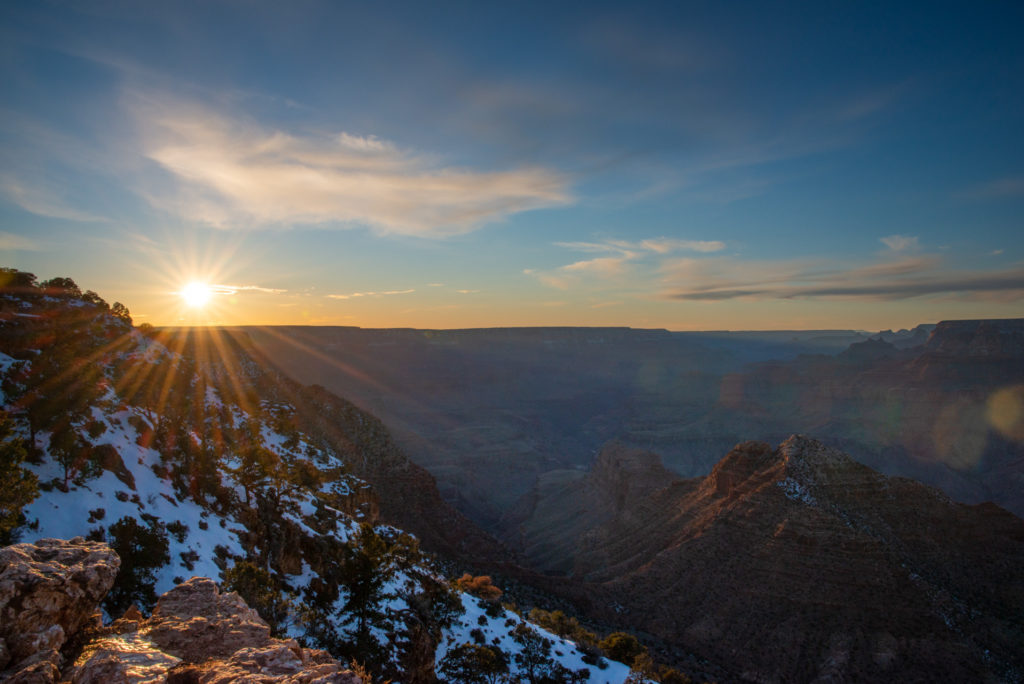 landscape with sun flare during a winter sunset at the grand canyon in arizona, photographed by jamie bannon photography.