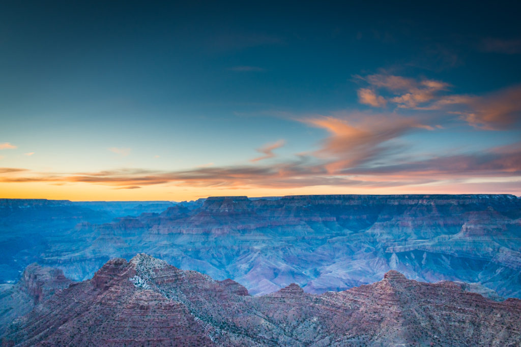 a winter sunset turns the grand canyon to colorful blues and purples under a pink, yellow, and orange sky, photographed by jamie bannon photography.